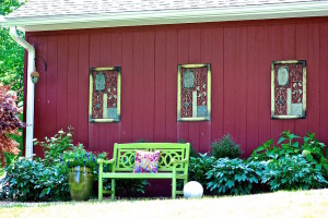 green garden bench on side of house