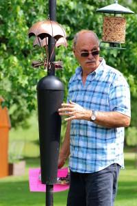 dad looking at squirrel-proof bird feeder